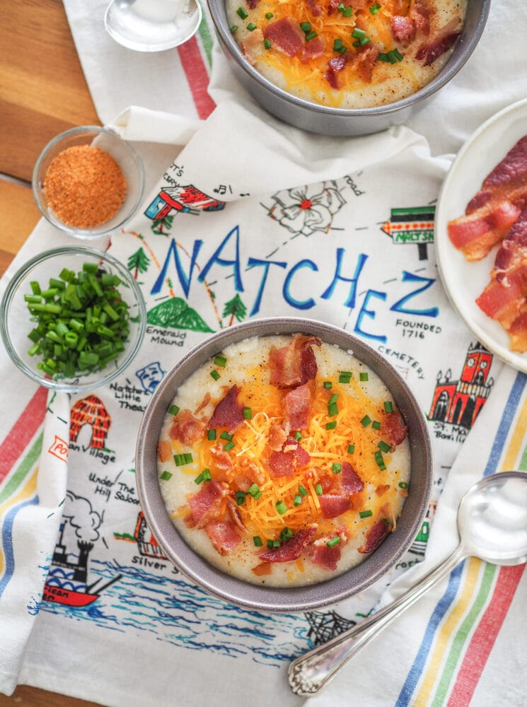 """Overhead shot of a bowl of grits topped with cheddar cheese, bacon, and chives displayed on a kitchen towel that says """"Natchez."""""""