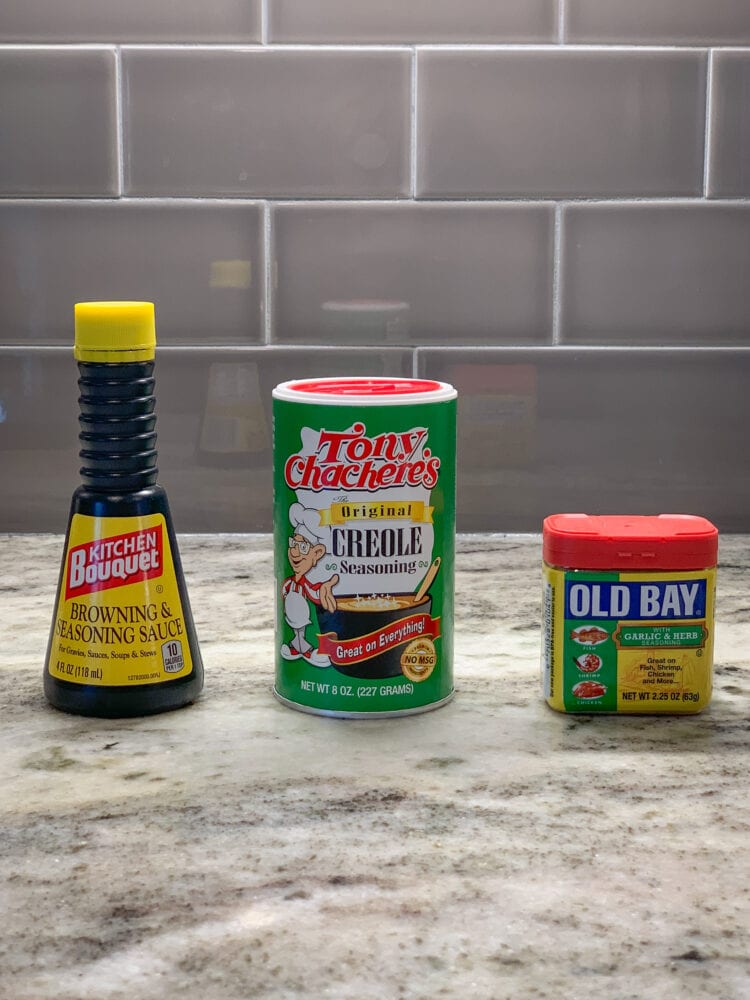 A photo of three different seasonings used for grits, Kitchen Bouquet, Tony Chachere's, and Old Bay.