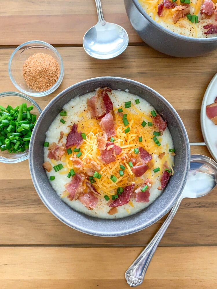 Overhead shot of a bowl of grits topped with cheddar cheese, bacon, and chives with pinch bowls of extra chives and seasoning on the side.