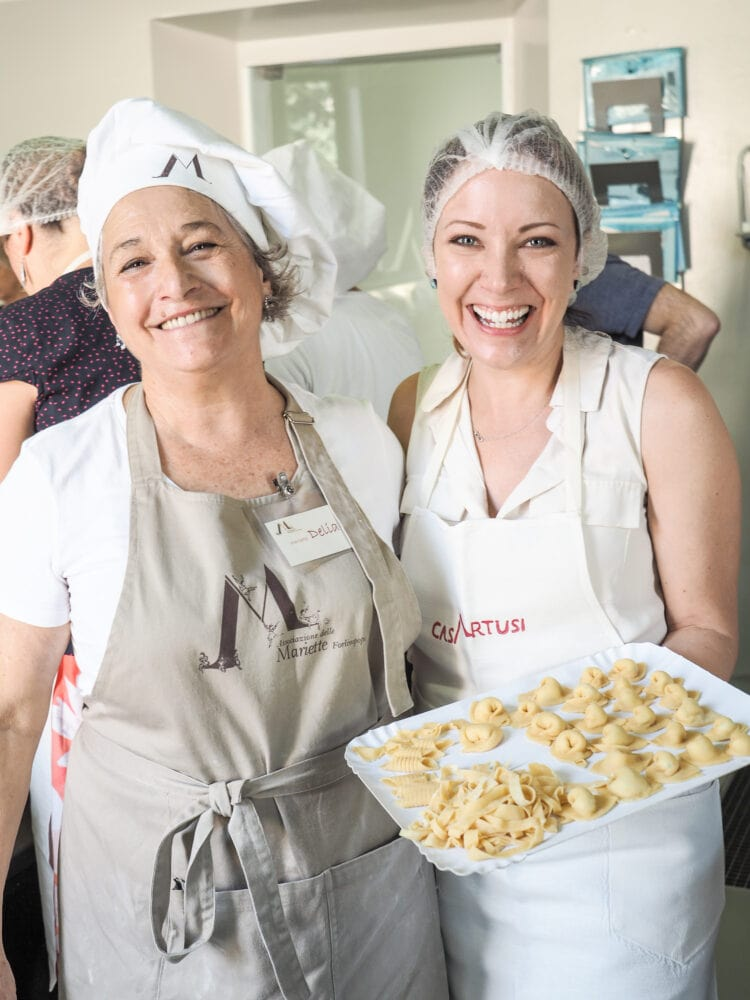 Delia and Rachelle smiling at the end of class while holding the finished pasta.