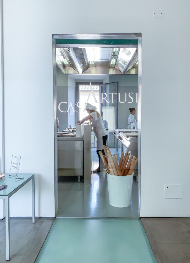 Glass entrance to the Casa Artusi cooking school with a bucket of pasta rolling pins and instructors working in the back.