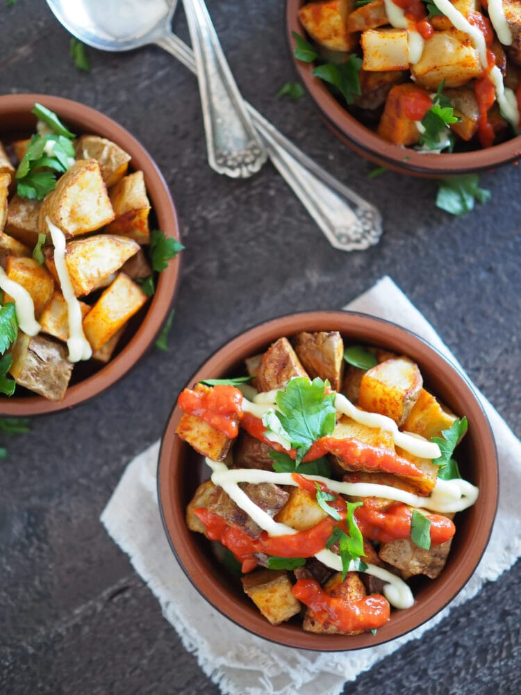 Patatas Bravas, a set of three terracotta dishes filled with oven baked potatoes, drizzled in salsa brava and aioli, and sprinkled with parsley.
