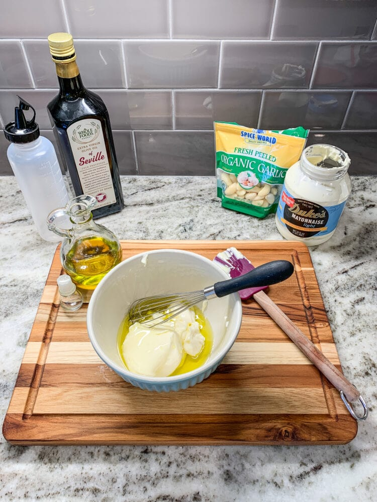 Making aioli, a bowl of mayonnaise and olive oil with garlic and squeeze bottle for serving in the background.