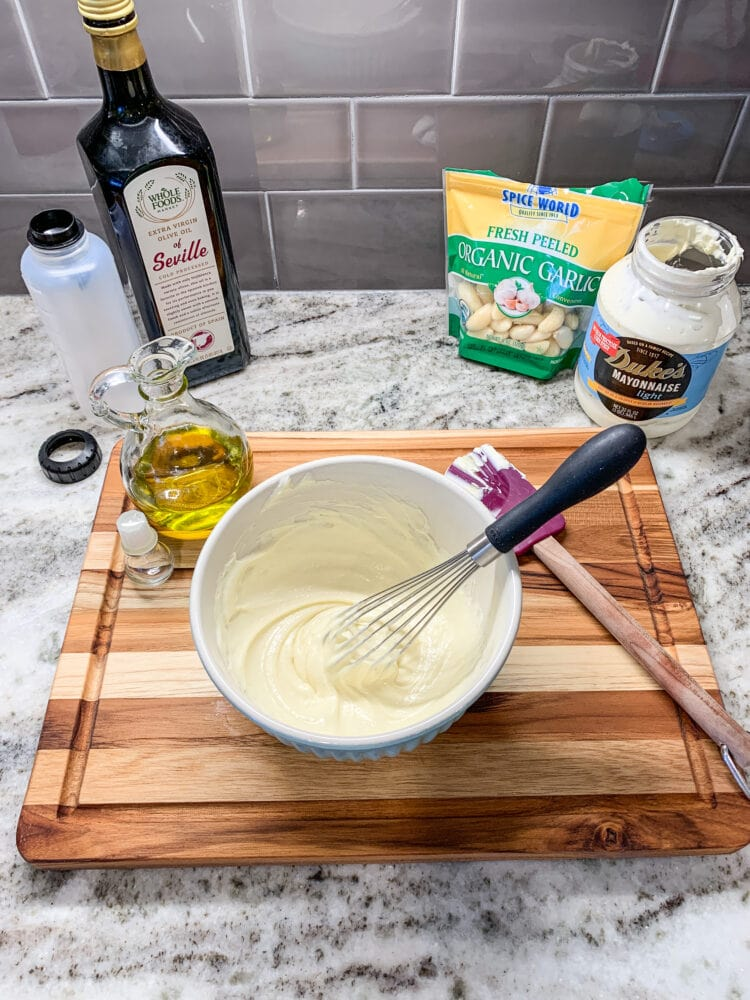 Making aioli, a bowl of mayonnaise and olive oil whisked together with garlic and squeeze bottle for serving in the background.