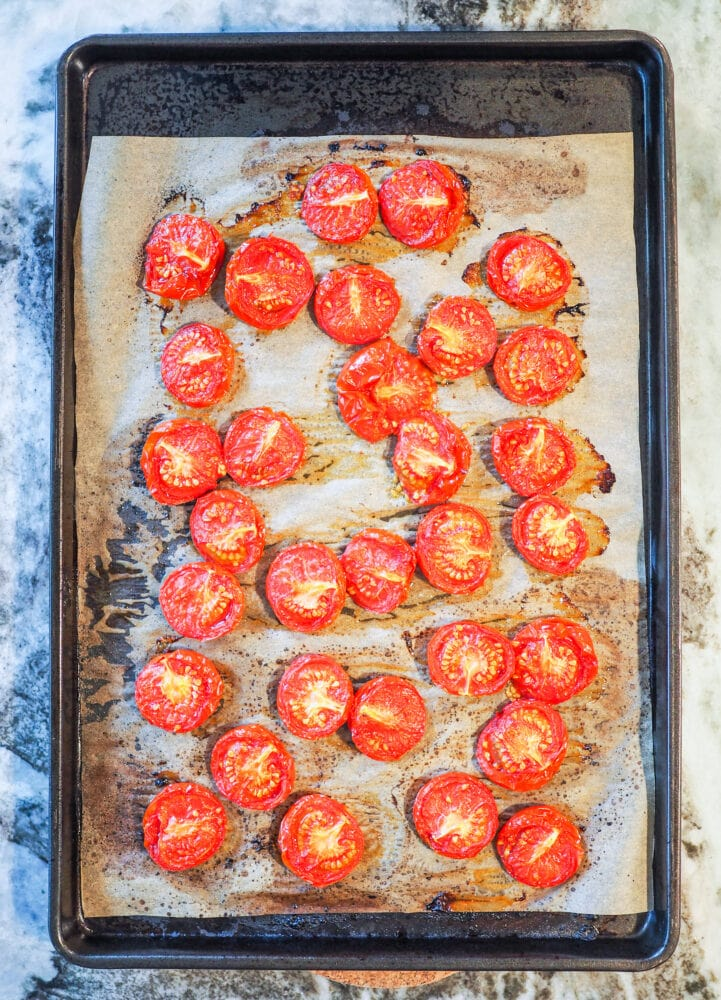 Overhead shot of sheet pan lined with parchment with oven roasted tomatoes.