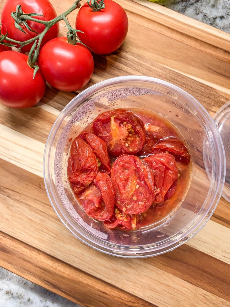 Making patatas bravas sauce ... Campari tomatoes, both raw and cooked, on a wood cutting board.