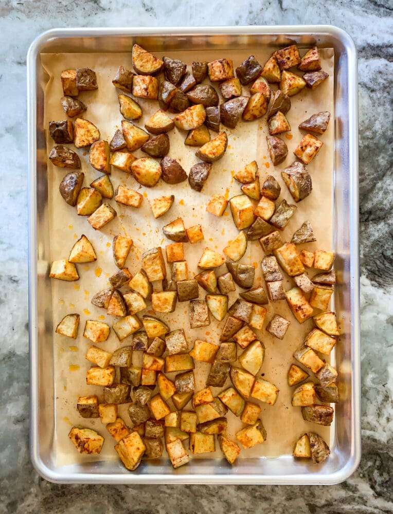 Overhead shot of sheet pan lined with parchment with oven roasted potatoes.