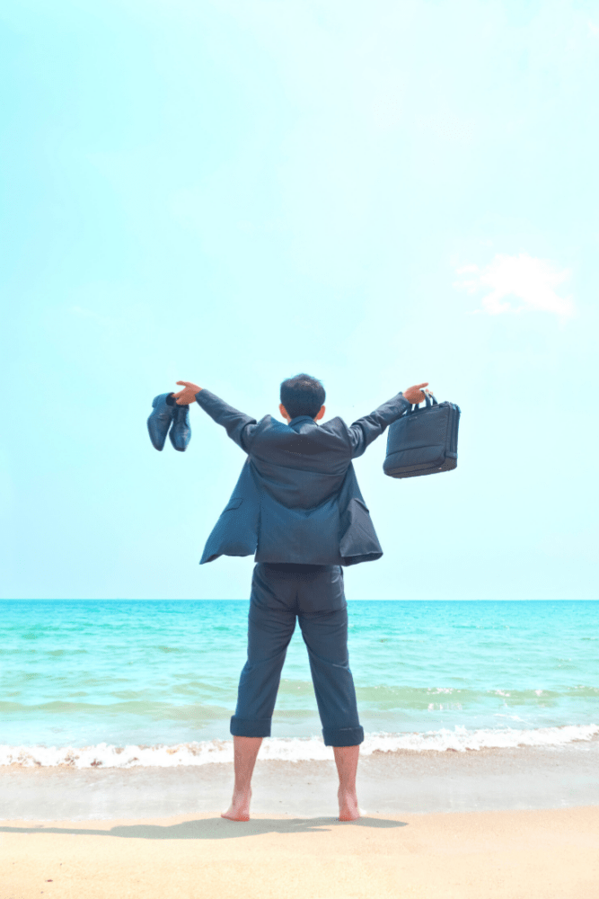 Man on beach facing ocean, wearing suit and holding up briefcase and dress shoes.