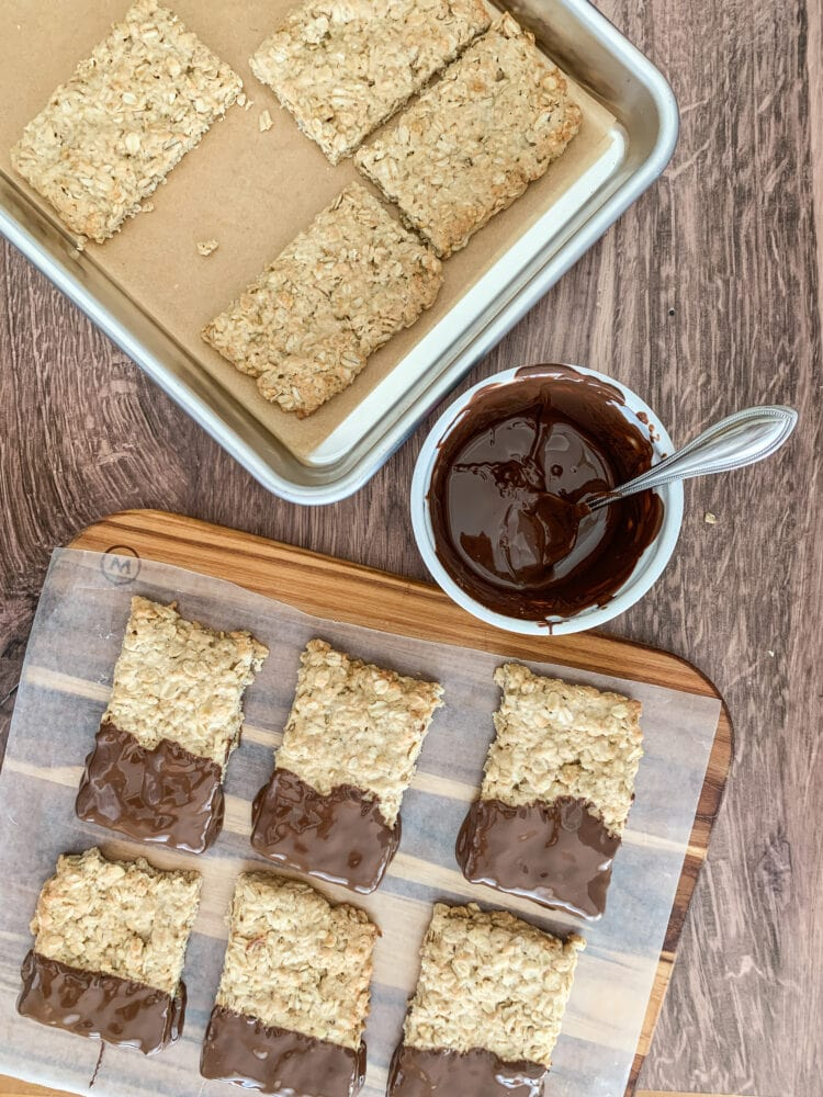 Baked oatcakes on a cookie sheet with a bowl of melted chocolate and chocolate dipped oatcakes cooling on wax paper.