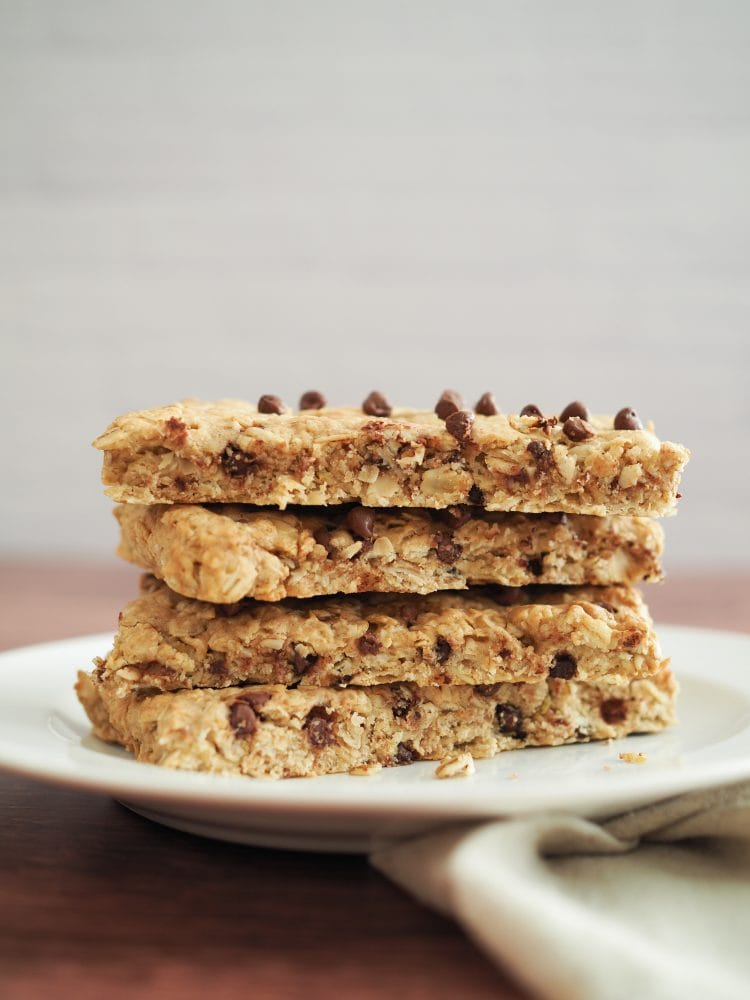 Side view of 4 chocolate chip oatcakes stacked on top of one another on a plate.