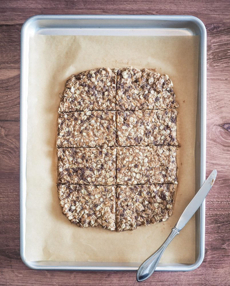 Unbaked dough rolled out into a rough rectangle shape with scoring down the center and from side-to-side to make 8 oatcakes.