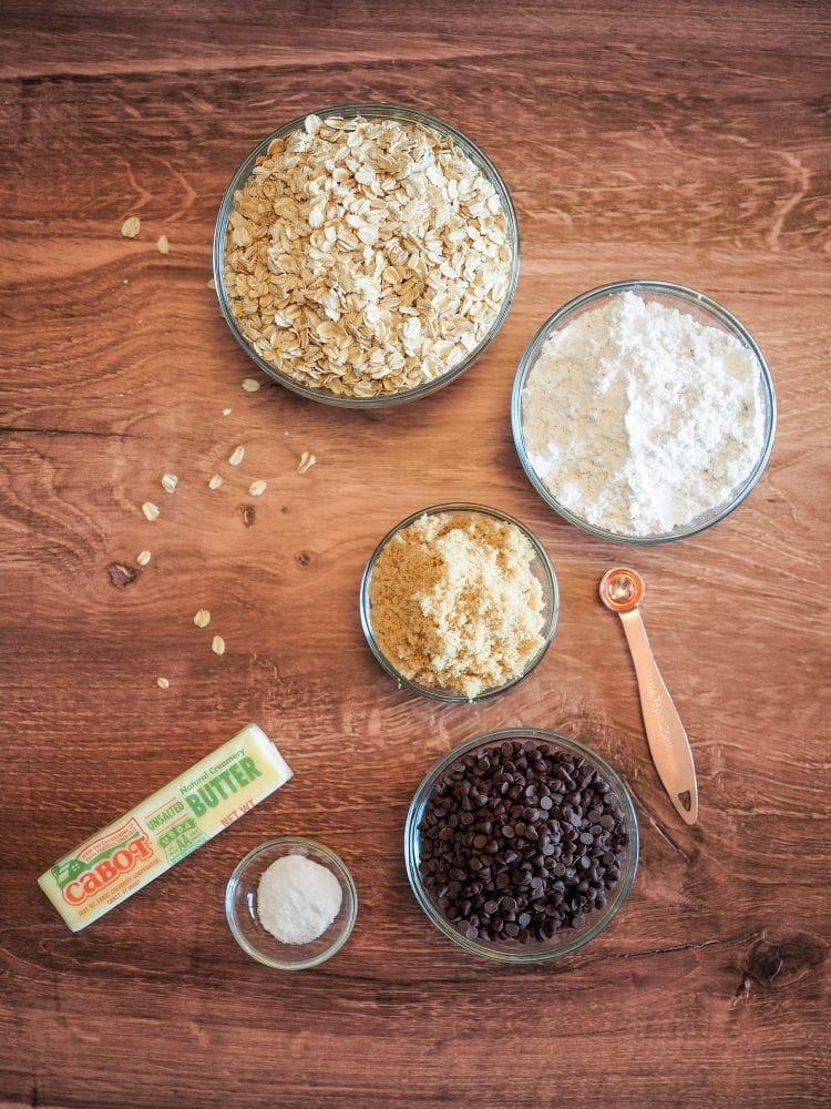 Overhead view of all the ingredients gathered together: oats, flour, brown sugar, chocolate chips, butter, and baking soda and salt.