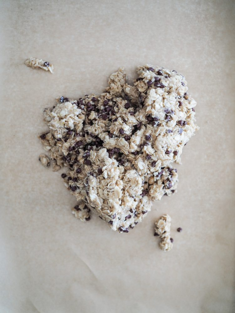 Oatcakes dough mixed with chocolate chips scooped out onto parchment paper on a cookie sheet.