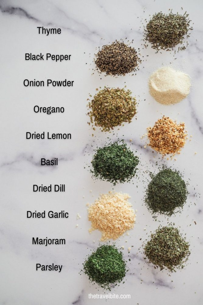Spices in little piles on a marble table showing thyme, black pepper, onion powder, oregano, dried lemon, basil, dried dill, dried garlic, marjoram, and parsley.