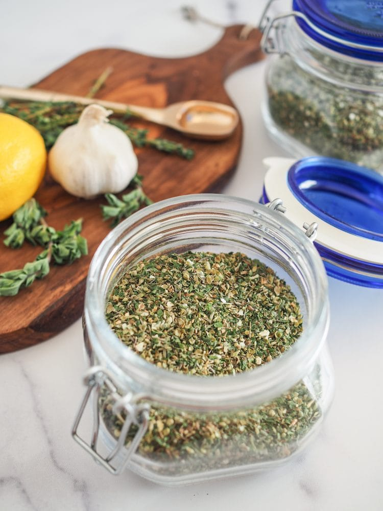 Open glass jar of blended Greek seasoning with a cutting board and fresh herbs and garlic in the background.
