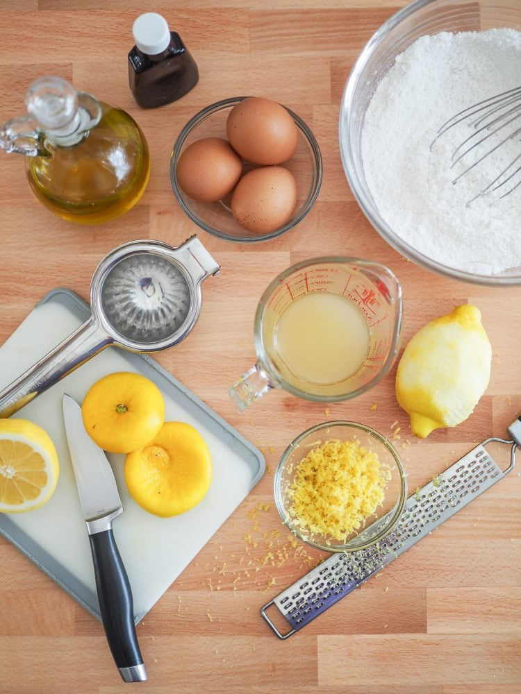 Overhead shot of zesting and juicing lemons into a separate bowl and measuring cup.