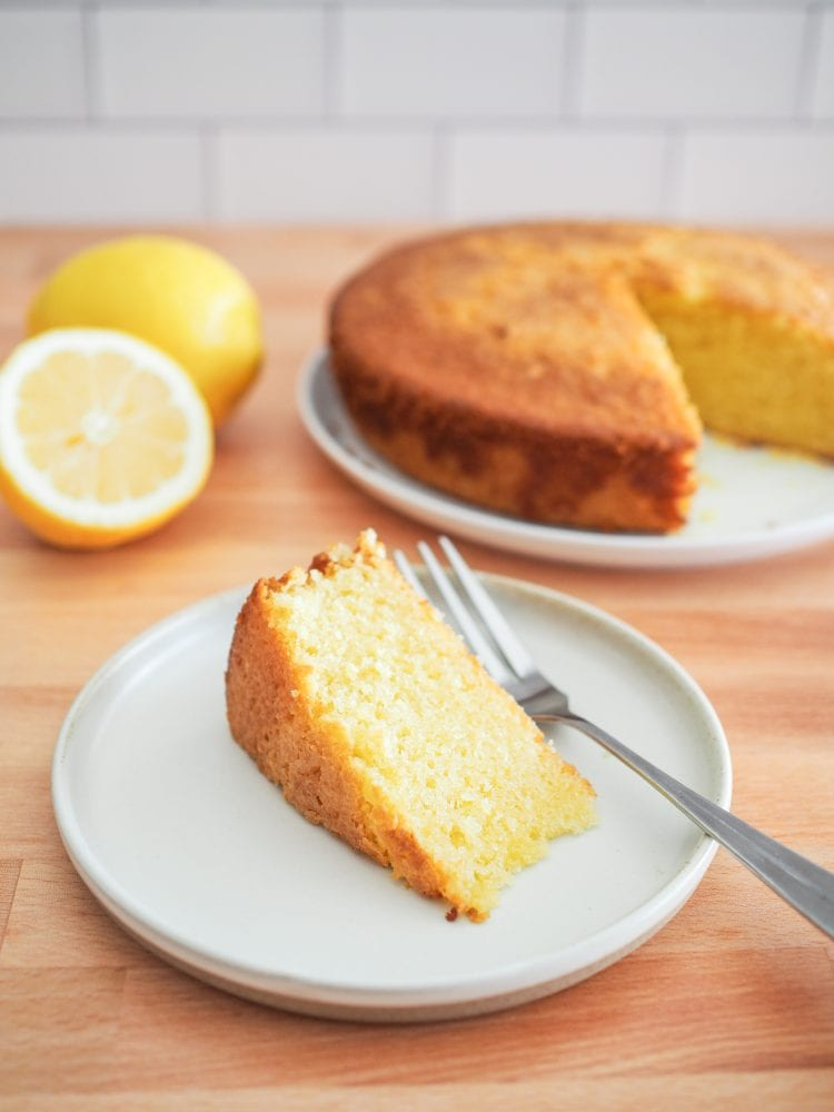 A slice of lemon olive oil cake on a plate with the whole cake in the background.