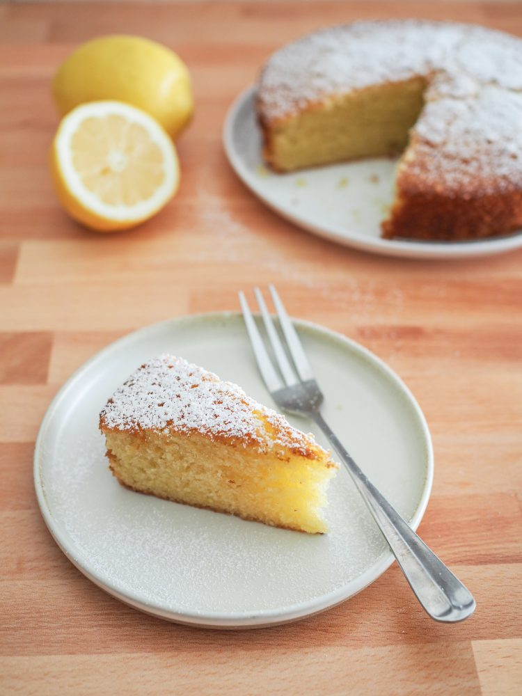 A slice of lemon olive oil cake sprinkled with powdered sugar on a plate with the whole cake in the background.