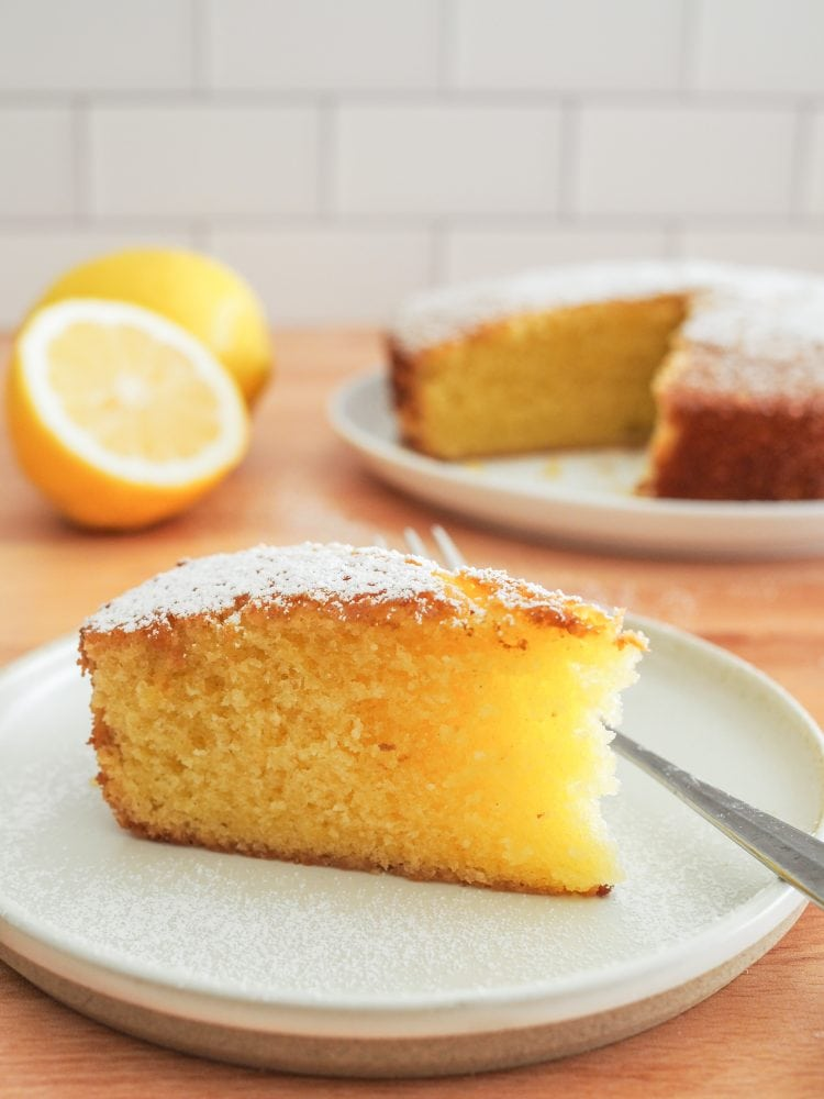 A slice of lemon olive oil cake sprinkled with powdered sugar showing the bright yellow lemon color and dense fluffy texture.