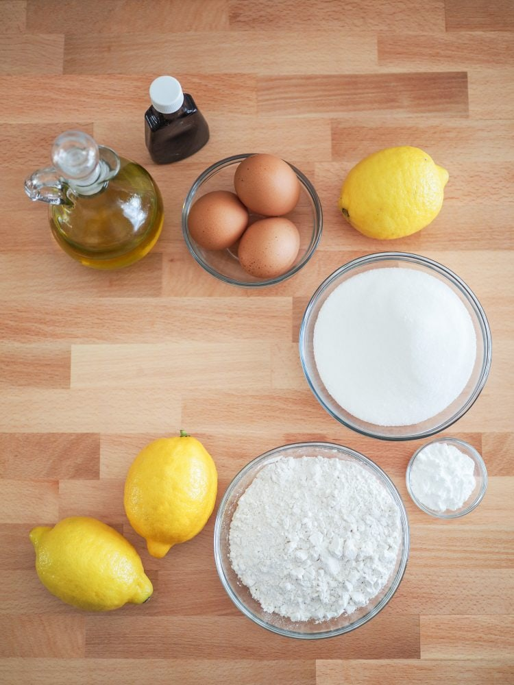 Overhead shot of ingredients for lemon olive oil cake including lemons, olive oil, lemon extract, eggs, sugar, flour, baking powder.