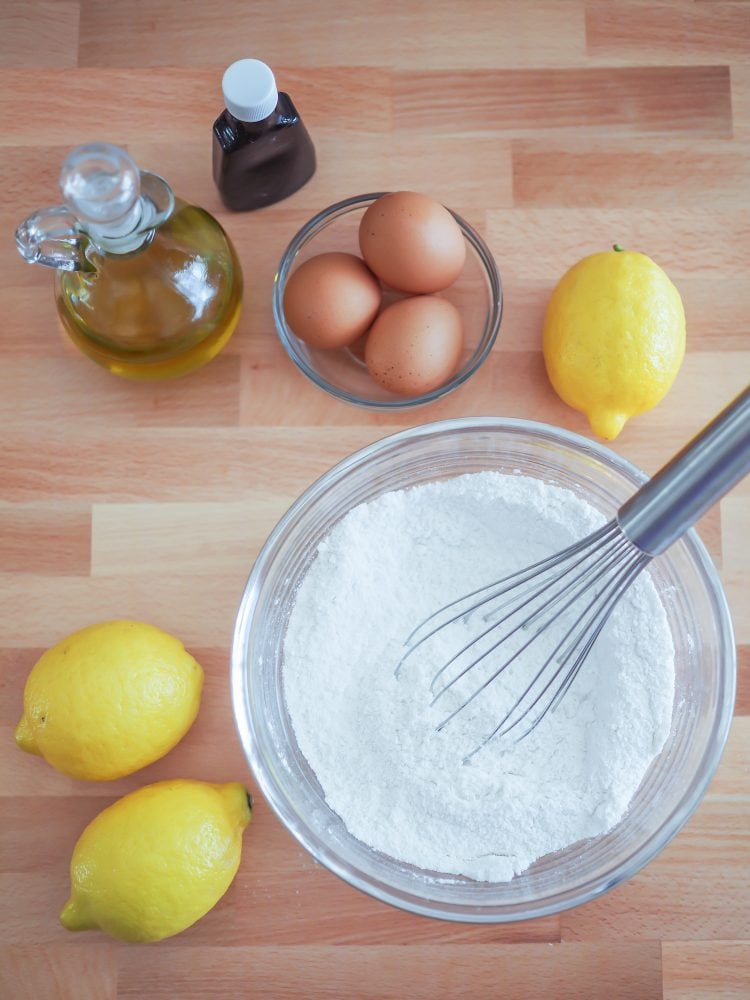 Overhead shot of mixing together the flour and baking powder in a bowl with eggs, oil, and lemons in the background.