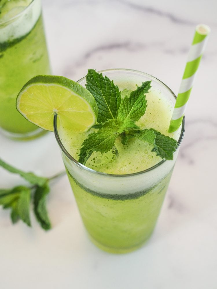 A glass of mint lemonade with slice of lime and sprig of mint as garnish, and a green and white paper straw.