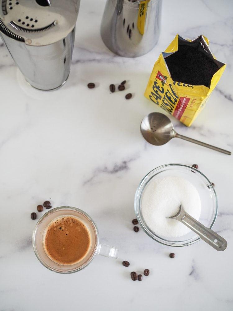Shakerato recipe ingredients and materials: martini shaker, finely ground espresso, sugar, and freshly brewed espresso.