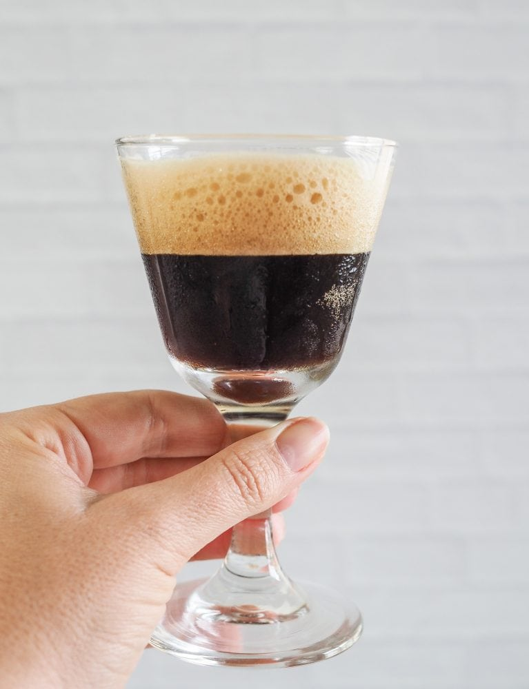 Holding up a shakerato to show the side view with the frothy crema on top.