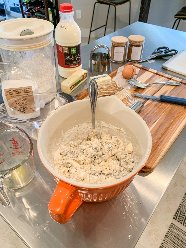 Side shot of mixing the dough for Welsh Cakes with a bowl of dough, and flour, sugar, milk, butter, and egg, and spices in the background.