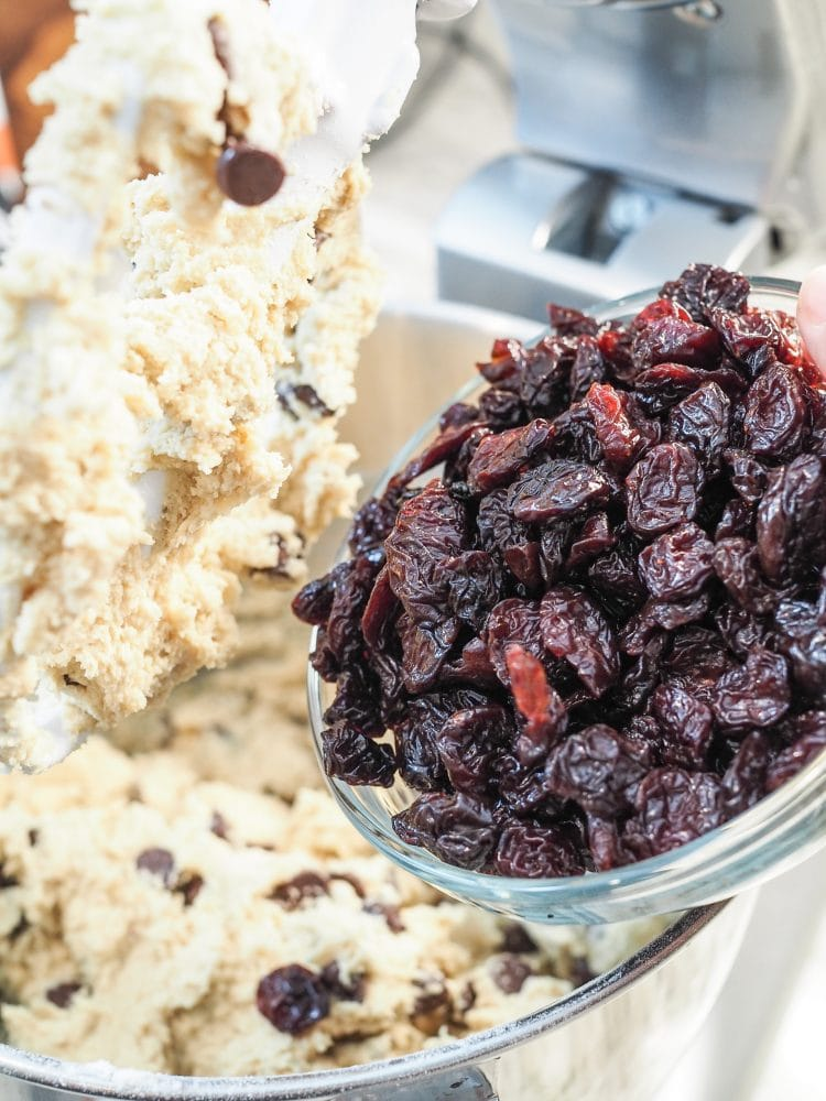 Adding dried cherries to cookie dough.