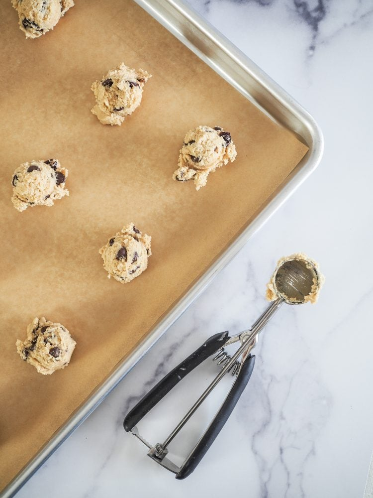 Scooping cookies onto baking sheet with small cookie scooper.