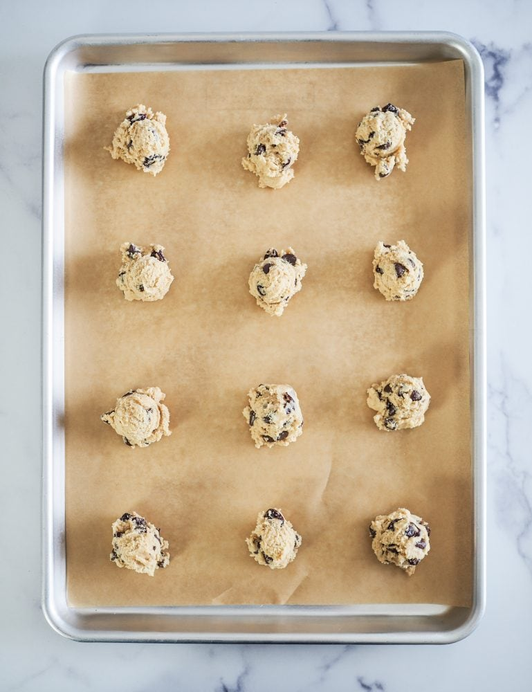 Parchment covered baking sheet with a dozen raw cookie dough balls ready to be baked.