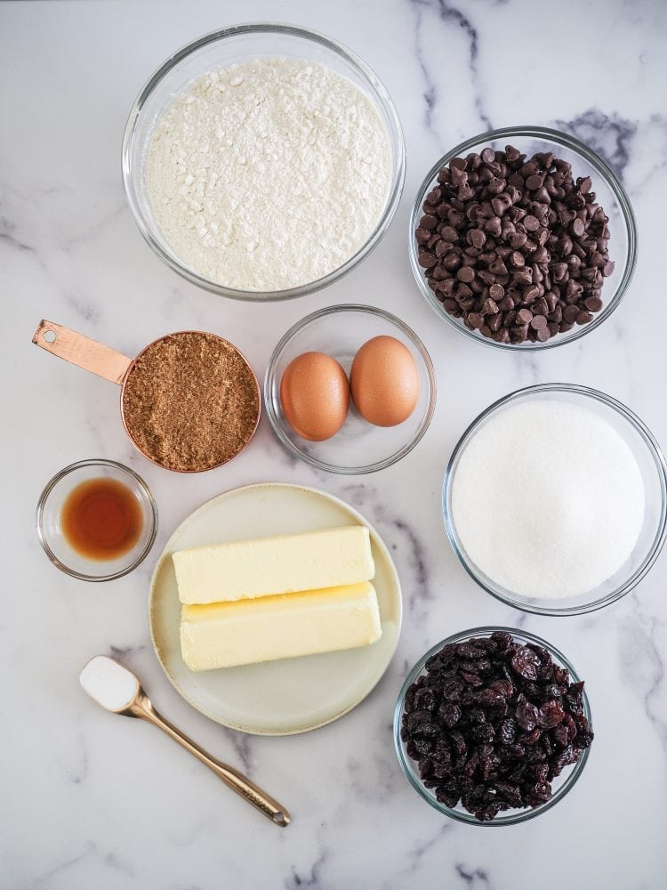 Overhead shot of ingredients to make cherry chocolate chip cookies including flour, chocolate chips, eggs, brown sugar, regular sugar, vanilla, butter, baking soda, and dried cherries.