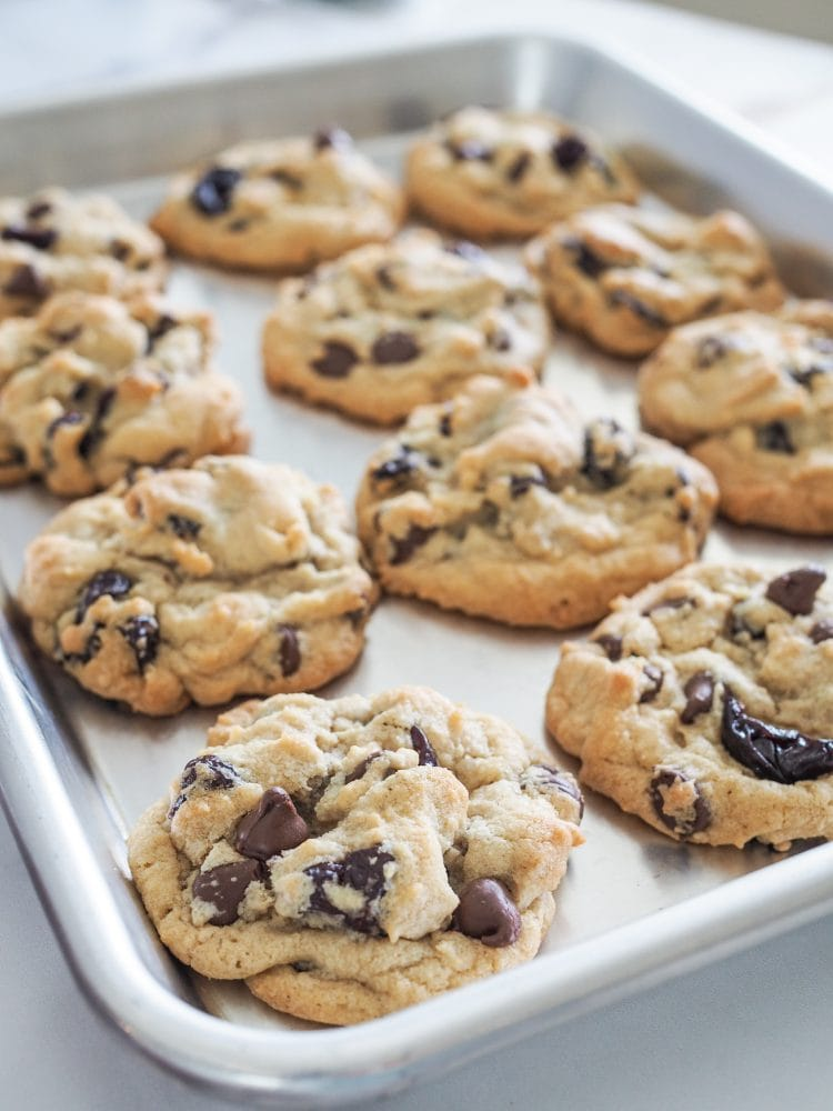 Baked cherry chocolate chip cookies on a sheet pan.