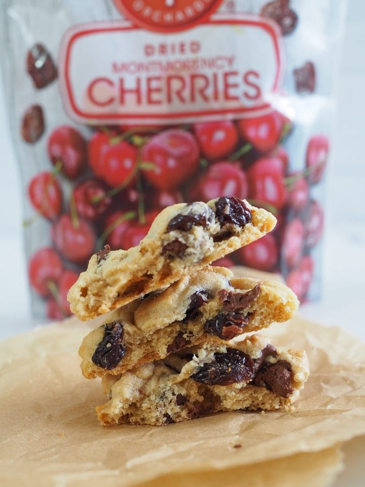 Side view of cherry chocolate chip cookies split in half with a bag of dried Montmorency cherries in the background.