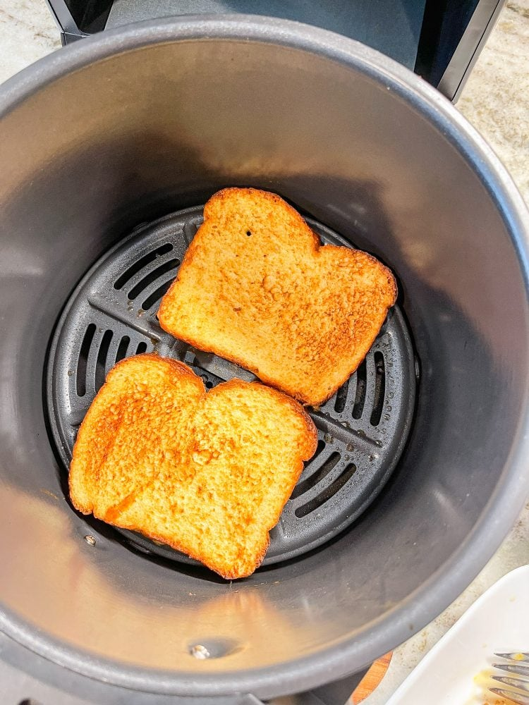 Two slices of air fried French toast in a round Ninja XL air fry basket.