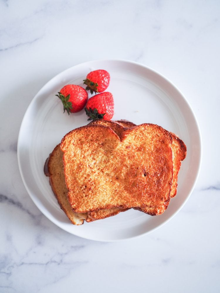 Three slices of air fried French toast on a white plate with strawberries.