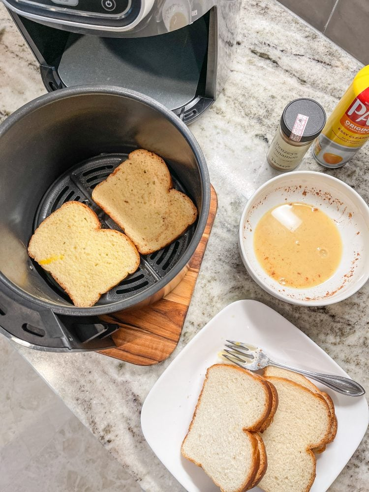 Two pieces of French toast in an air fry basket before getting air fried. The French toast batter and dry bread slices are on the side.