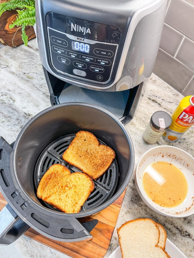 Overhead view inside Ninja air fry basket showing two pieces of air fried French toast, with the batter and dry bread on the side ready to make some more.