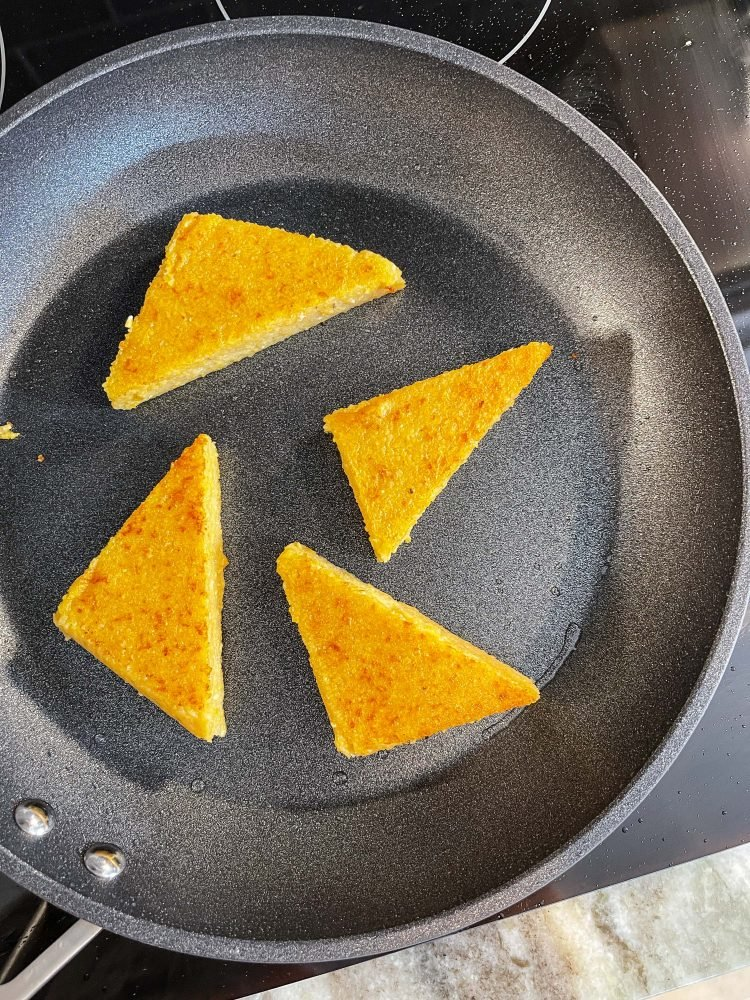 Triangular polenta cakes cooking in a frying pan.