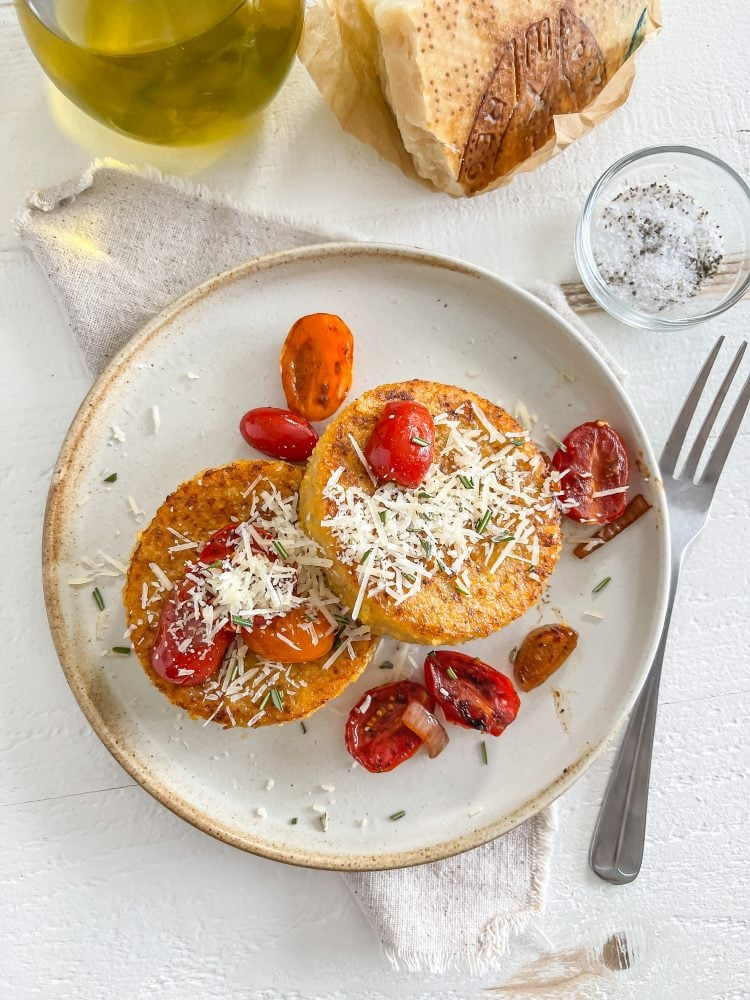 Overhead look at a plate with two round polenta cakes topped with Parmesan cheese and cherry tomatoes.
