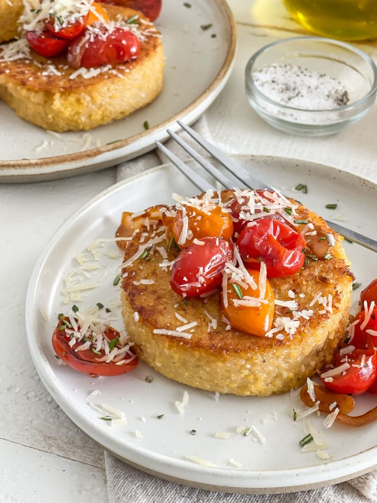 Side view of single polenta cake topped with sautéed cherry tomatoes, parmesan cheese, and chopped rosemary.