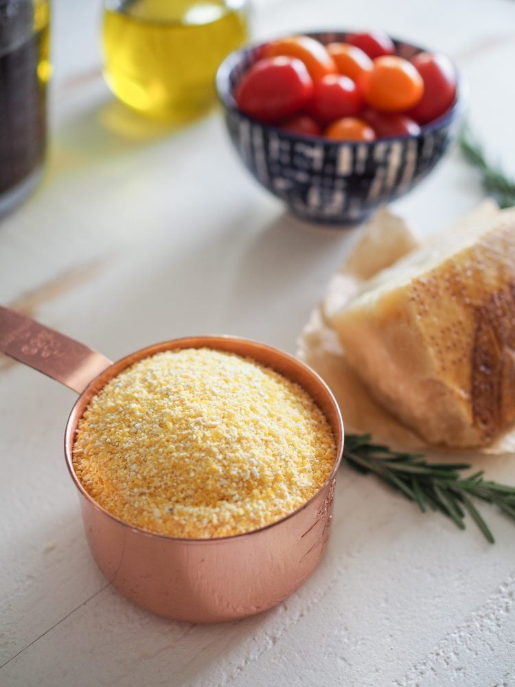 A copper measuring cup filled with course ground yellow cornmeal. A bowl of cherry tomatoes, jar of olive oil, sprigs of rosemary, and chunk of Parmesan cheese in the background.
