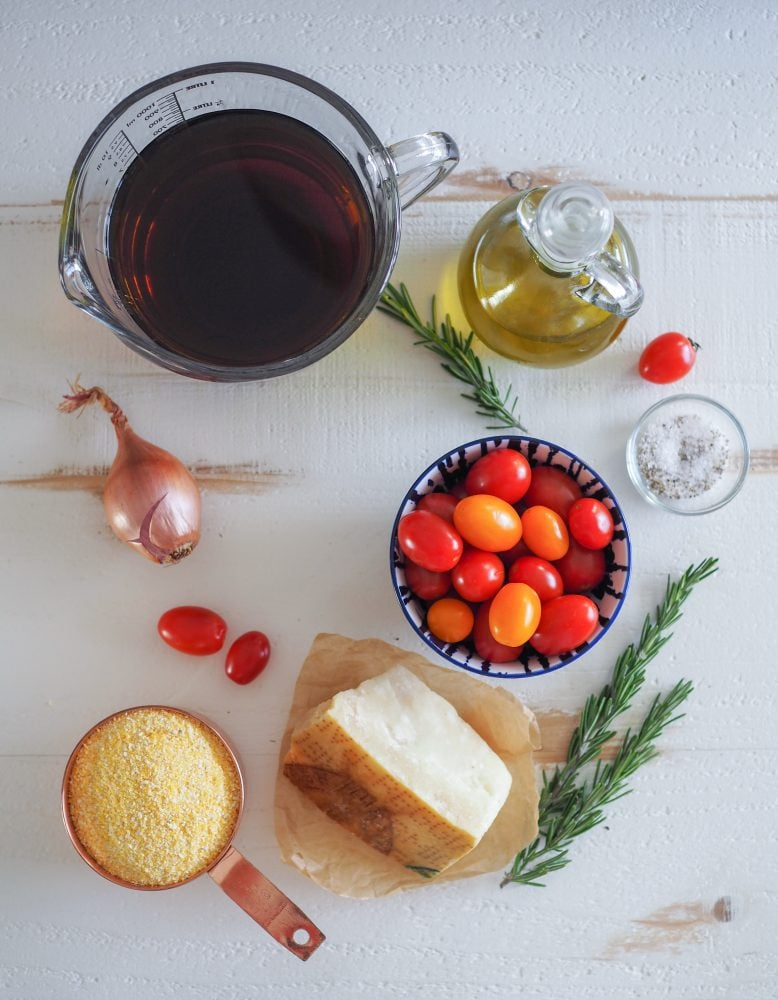 Overhead shot of all the ingredients used in making polenta cakes including vegetable broth, olive oil, rosemary, salt and pepper, shallot, cherry tomatoes, Parmesan cheese, and course ground cornmeal.